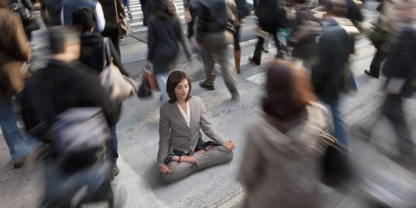 Mixed race businesswoman practicing yoga in busy urban crosswalk